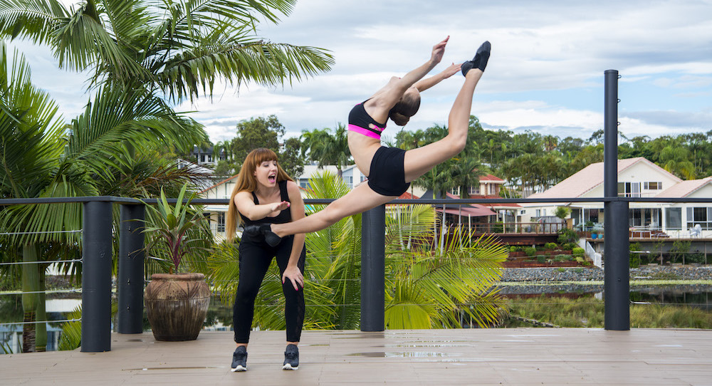 Lucy Ellis with a student in a firebird leap. Photo courtesy of Ellis.